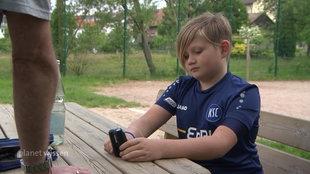 Junge sitzt auf Parkbank und misst seinen Blutzuckerspiegel