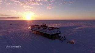 Die Forschungsstation Neumayer III in der Weite der Antarktis mit untergehender Sonne.