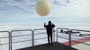 Ein Forscher der Neumayer Station III startet einen Wetterballon in der Antarktis.