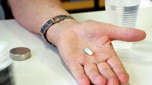 Auf einer geöffneten Hand liegt eine Tablette.