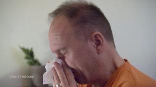Ein Mann putzt sich die Nase mit einem Papier-Taschentuch.