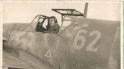 Schwarzweißfoto eines Wehrmachtpilotens in seinem Flugzeug.