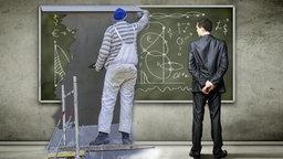 Ein Handwerker verputzt eine Schultafel auf der mathematische Symbole stehen. Neben ihm steht ein Mann im Anzug.