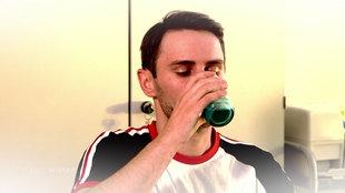 Ein junger Mann trinkt aus einem Glas.
