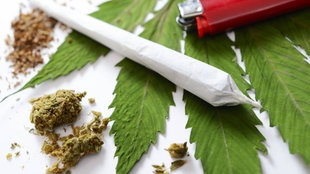Ein fertig gedrehter Joint liegt zusammen mit Marihuana und einem Feuerzeug auf einem Hanfblatt.