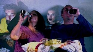 Eine Frau und ein Mann sitzen auf dem Sofa und trinken beide aus einer Flasche Bier.