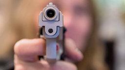 Der Lauf einer Pistole zielt in die Kamera