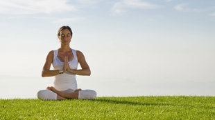 Eine Frau macht auf einer Wiese Yogaübungen