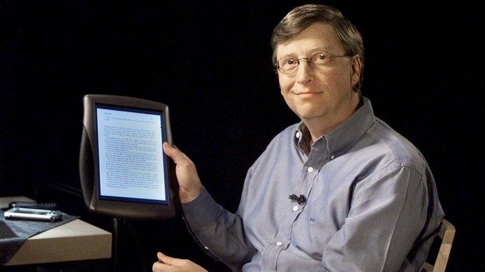 Bill Gates hält einen Tablet-PC in der Hand.