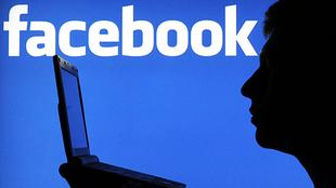 Im Vordergrund ist die Silhouette eines Mannes zu sehen. Er sitzt vor einem Laptop. Im Hintergrund ist das Facebook-Logo groß abgebildet.