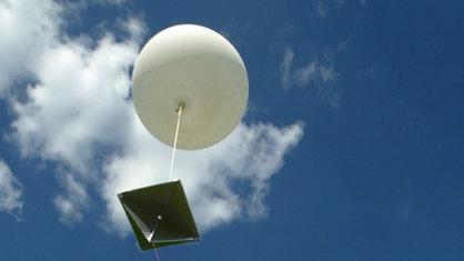 Mann hlät einen großen weißen Ballon