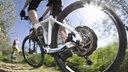 Hinterrad eines weißen E-Mountainbikes groß, vorne ein weiterer Radler am Berg