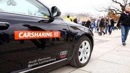 Carsharing-Fahrzeug, an dem Menschen vorbeigehen