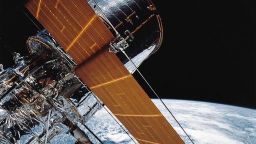 Das Foto zeigt Teile des riesigen Hubble-Weltraumteleskops. Im Hintergrund sind das All und die Erde zu sehen.