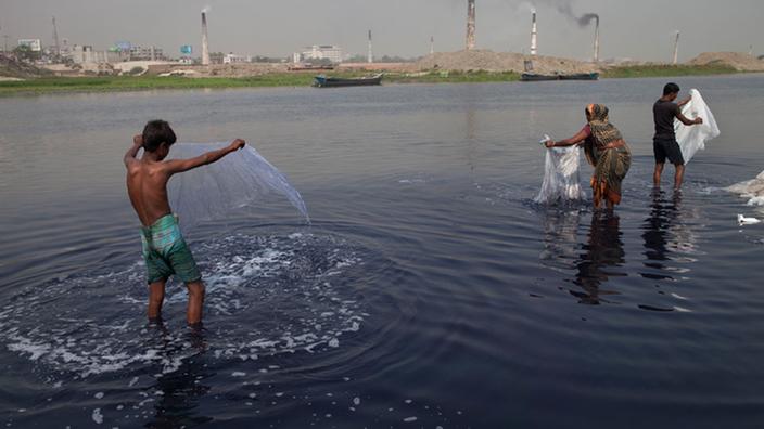 Tres bengalíes lavan bolsas de plástico en un río.