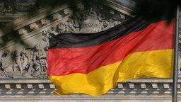 """Die Deutschland-Fahne weht vor dem Reichstag in Berlin, auf dem der Spruch """"Dem deutschen Volke"""" zu lesen ist."""