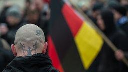 Skinhead mit tätowiertem Hinterkopf und Deutschlandfahne.