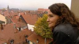 Vera Kühne steht auf einem Balkon und schaut auf die Stadt.