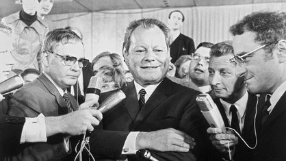 Willy Brandt lächelt am Wahlabend 1969 in die Kameras