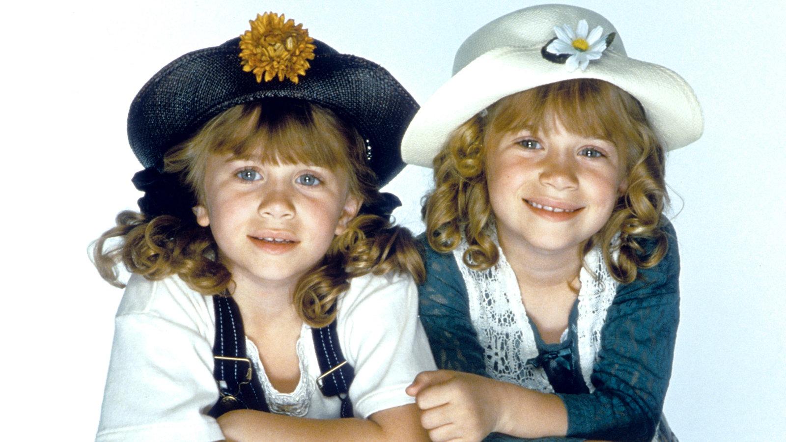 Ashley und Mary-Kate Olsen im Alter von acht Jahren bei einer Fotosession, beide Kinder mit Hut.